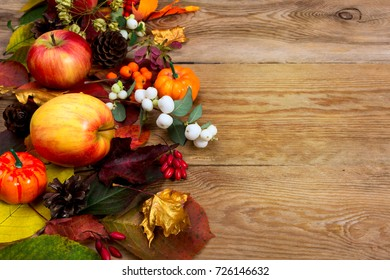 Fall greeting background with apples, white berries, golden maple leaves on the old wooden table, copy space