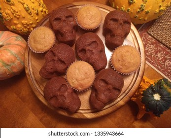 fall or Halloween baking featuring pumpking bread skulls with seasonal gourds and wood background