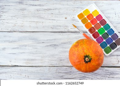 Fall Halloween crafts. One orange decorative pumpkin and bright paint with brush on white wooden background. Jack O Lantern Pumpkin on table ready for painting