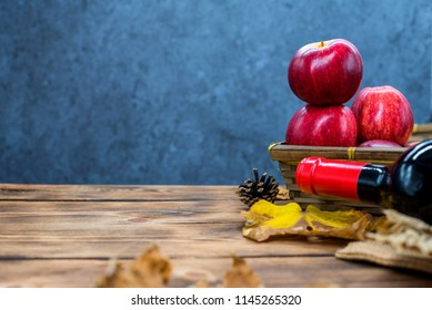 Fall harvest cornucopia. Basket with red apple and red wine on the wooden table. Copy space on dark background in Autumn season.