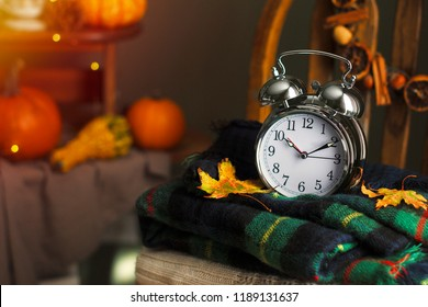 Fall is here,  autumn time, colorful tartan plaids woolen textile on wooden stool chair, fall wreath, alarm clock rustic black background