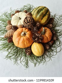 Fall holiday still life with mini pumpkins of different colours, pine cones, green branches and acorns. White background, home decor, house decorating