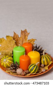 Fall holidays - Halloween and Thanksgiving. Still life - candles and pumpkins, pine cones, nuts, leaves.