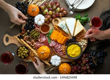 Fall holidays party table with friends hands picking some fingerfoods from charcuterie board, top down view
