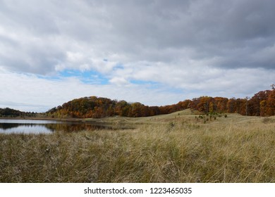 Fall landscape in the Midwest with lake, clouds, and grass with fall leaves on trees