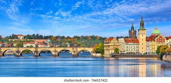 Fall landscape view to Charles bridge on Vltava river in Prague Czech republic with blue sky and withe clouds.