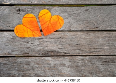 Fall leaves. Autumn hearts. Love background on wooden board, with copy space.
