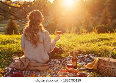 Fall picnic Outdoors. Perfect autumn warm day, autumn picnic in nature. Girl Autumn Picnic. Girl sitting on plaid with basket of  products and a bottle of young red wine is enjoying sunny day.