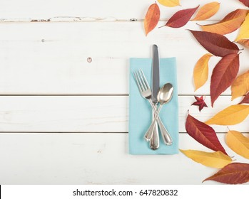 Fall Place setting with Colorful Leaves, a Teal Cloth Napkin and Silverwarel on distressed white shiplap board background with room or space for copy, text, or words.  It's a flat lay and horizontal