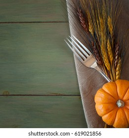 Fall Place setting with a Silver Fork, Mini Pumpkin, and Wheat Grass on a Brown Napkin on Distressed Green Board Table Background with room or space for copy or your words.  Its square and moody