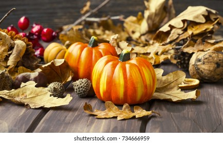 Fall pumpkins decoration with dried leaves, acorns, chestnuts