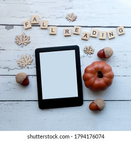 Fall reading:  top view of an emptyebook on a rustic white wood surface surrounded by fall themed items and wooden letter tiles . autumn themed ereader flat lay with copy space