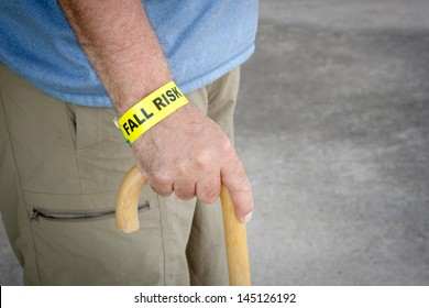 Fall risk bracelet around an elderly man's wrist while walking with a wooden cane