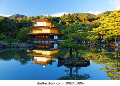 Fall scenery of beautiful Kinkakuji, a famous Zen Buddhist temple in Kyoto Japan, with Golden Pavilion glittering under blue clear sky and reflected in the peaceful lake water on a sunny autumn day