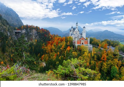 Fall scenery of fairy-tale New Swan Stone Castle (Schloss Neuschwanstein) perched on a rugged hill & surrounded by autumn colors in the beautiful landscape of Bavarian countryside near Fussen, Germany