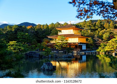 Fall scenery of Kinkakuji, a famous Zen Buddhist temple in Kyoto, Japan, with the majestic Golden Pavilion glittering under blue clear sky & reflected in the peaceful lake water on a sunny autumn day