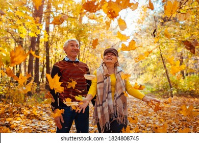 Fall season. Family couple throwing leaves in autumn forest. Senior people having fun outdoors enjoying nature