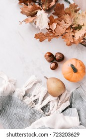 Fall season flatlay in pastel colors for fashion and beauty, lifestyle bloggers, announcements, ads. Wool scarf with fringe, dry leaves, acorns, little pumpkin, pear. Copy space
