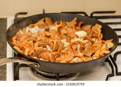 Fall season. Mushroom hunt. Saffron milk caps aka red pine mushrooms aka Lactarius deliciosus frying in a frying pan with brown onion.