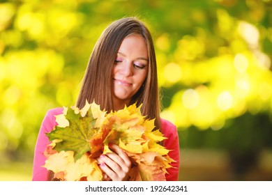 Fall season. Portrait of happy girl young woman with bunch of colorful leaves in autumnal park forest. Outdoor.