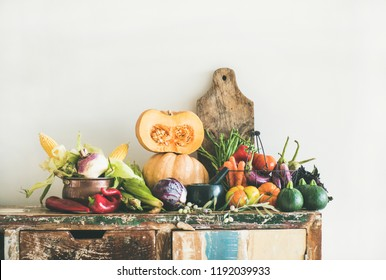 Fall seasonal vegetarian food ingredients variety. Assortment of Autumn vegetables for healthy cooking over rustic kitchen cupboard, white wall background, copy space. Local market organic produce
