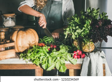 Fall seasonal vegetarian or vegan dinner cooking. Female in linen apron cutting various vegetable ingredients on concrete kitchen counter. Slow food, comfort food, healthy diet, clean eating