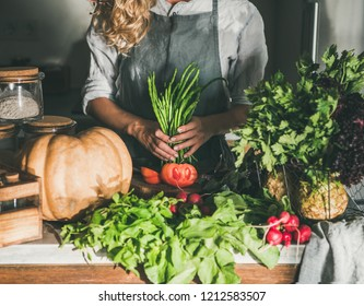 Fall seasonal vegetarian or vegan dinner cooking. Female in linen apron preparing green beans for cutting on concrete kitchen counter. Slow food, comfort food, healthy diet, clean eating