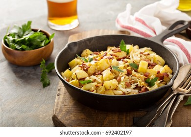 Fall side dish with fried cabbage, potatoes and bacon in a cast iron pan