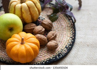 Fall Still Life with Mini Pumpkin, green apple,walnuts and delicata sweet dumpling squash.  A horizontal with side copy space in natural window light.