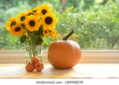 Fall Still Life Photo with Sunflower bouquet and Pumpkins in Window Natural Light with room or space for copy, text or your words or design elements.  Horizontal taken with side view