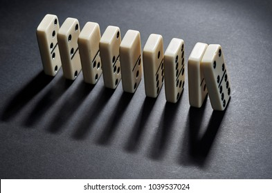 Fall stop. A series of dominoes on a black background.