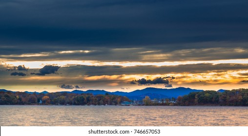 Fall sunset on Shelburne Bay at Lake Champlain in Burlington Vermont.  Vivid fall colors with a shipyard in the distance