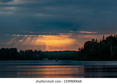 Fall sunset over a northern Minnesota fishing lake, silhouetting the forest surrounding it and casting sun rays on the water and a passing fishing boat