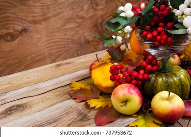 Fall table centerpiece with snowberry and rowan berries, green pumpkin, oak leaves and apples on the rustic wooden background, copy space