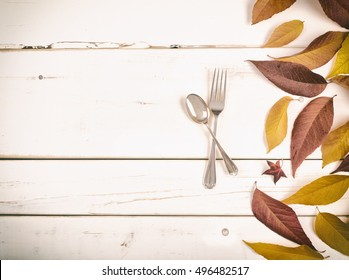 Fall Table Place setting with fork and spoon in Sepia Brown Toned Ash Leaves for a Thanksgiving or Halloween Card on Rustic White Wood Board Background with room or space for copy, text, or your words