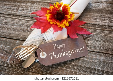 Fall Table Place Setting with Name card with Happy Thanksgiving text, white napkin, silverware, and flower, on rustic wood background.  Horizontal photo with looking-down view with flatlay design