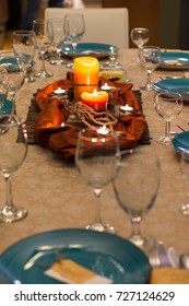 Fall table set with blue plates, wine glasses and a glowing orange candle centerpiece