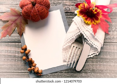 Fall Table Setting with Blank Invite or Menu Card with space or room for your copy, text or design.  A fork and knife in Vintage Napkin, flower, and red bow done with Old Fashioned Toned Processing.