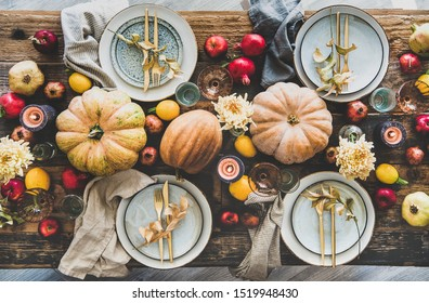 Fall table setting for Thanksgiving day party or family gathering dinner. Flat-lay of plates, silverware, floral and fruit decoration, candle and pumpkins over rustic wooden table background, top view