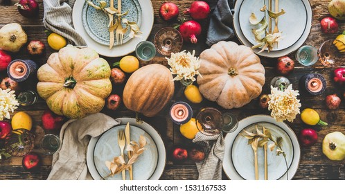 Fall table setting for Thanksgiving day or family dinner. Flat-lay plates, silverware, floral and fruit decoration, candle and pumpkins over rustic wooden table background, top view, wide composition