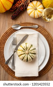 Fall Thanksgiving dinner table place setting home decorations with ceramic dishes, silverware, cloth napkin, white wine and ornamental squash on rustic wooden tabletop. Holiday entertaining parties.