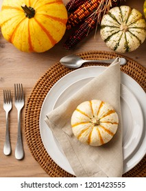 Fall Thanksgiving dinner table place setting home decorations with ceramic dishes, silverware, linen cloth napkin and ornamental squash on rustic wooden tabletop. Holiday entertaining parties.