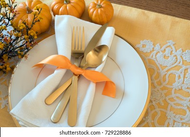 Fall Thanksgiving or Halloween Table Place Setting and pumpkins in Gold tones. Horizontal with natural lighting from above, looking down view. Has room or space for copy, text, words or design on side