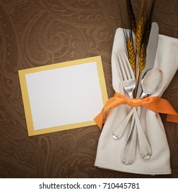 Fall Thanksgiving Place Setting with Silverware, Napkin, orange ribbon, and a name card on Elegant Brown Table Cloth with blank room for copy, text or words.  A square crop, flat lay with above view