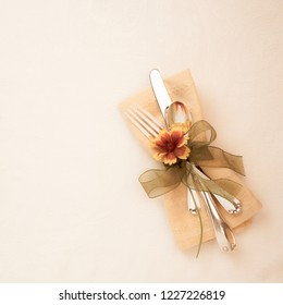 Fall and Thanksgiving Table Place Setting in Soft Golden Cream Tones with Cloth Napkin, Flower, and Silverware on Tablecloth with room or space on side for Copy, text or words and is a Square Flaylay