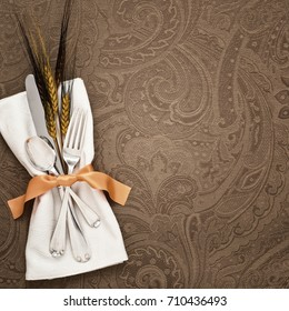 Fall Thanksgiving Table Place Setting with Silverware, orange ribbon napkin ring and wheat decoration on brown cloth with room for copy, text words or design. A square crop with dark moody tone