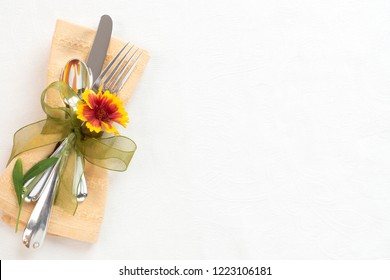 Fall Thanksgiving Table Setting with Silverware, pretty Mum Flower, and gold napking on White Damask Cloth with room or space for copy, text or your words.  It's horizontal flatlay with above view