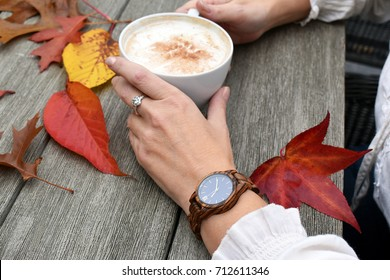 Fall Time - Modern woman wearing watch and holding a cup of coffee on a rustic wooden table with colorful Autumn leaves