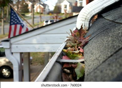 A fall tradition - cleaning the gutters of leaves. Here, we see them clogging the gutters of a traditional home. Narrow DOF used for advertising/clean up articles/etc.