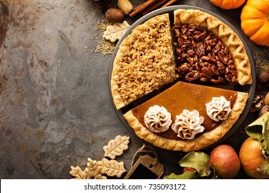 Fall traditional pies pumpkin, pecan and apple crumble pie overhead shot with copyspace